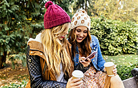 Two young women with smartphone in a park in autumn - MGOF02616