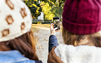 Two young women taking a selfie in a park in autumn - MGOF02619