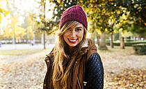 Portrait of smiling young woman wearing wooly hat in a park in autumn - MGOF02622