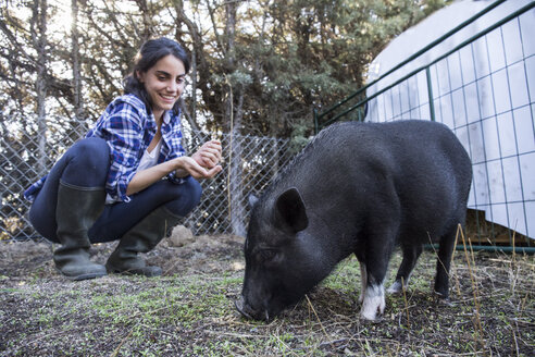 Woman with pig on a farm - ABZF01519