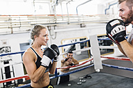 Female boxer sparring with coach - MADF01254