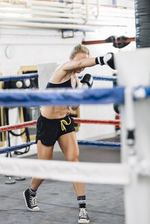 Female boxer punching in boxing ring - MADF01266