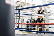 Portrait of confident female boxer in boxing ring - MADF01269