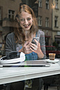 Portrait of smiling woman with smartphone in a coffee shop - TAMF00809