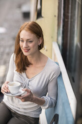 Redheaded woman drinking coffee at sidewalk cafe - TAMF00821