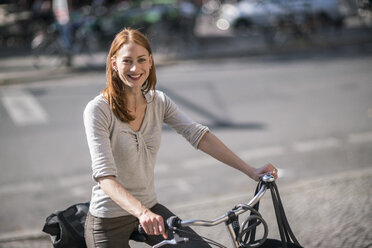 Portrait of redheaded woman with bicycle - TAMF00824