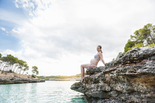 Pregnant woman sitting on rock at the sea - DIGF01425