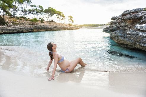 Pregnant woman sitting at the sea - DIGF01431
