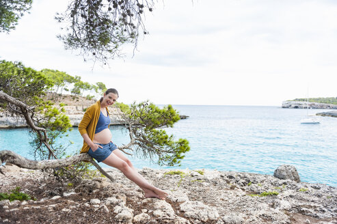 Smiling pregnant woman sitting on branch at the sea - DIGF01440