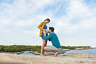Man kissing belly of pregnant woman at the sea - DIGF01452
