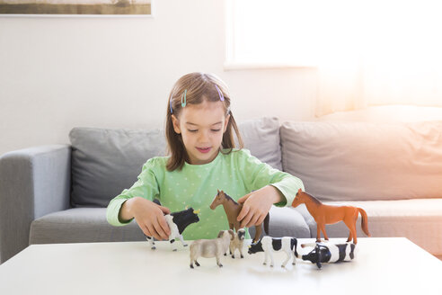 Little girl playing with animal figurines at home - LVF05590