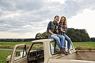Couple sitting on pick up truck having a beer - FMKF03215