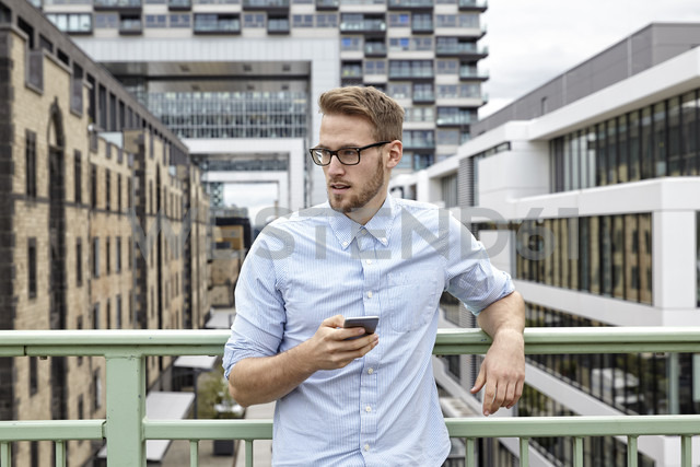 Young man with cell phone outdoors - FMKF03236