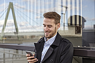 Smiling young man looking on cell phone outdoors - FMKF03239