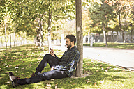 Man sitting on meadow in autumn looking at cell phone - JASF01287
