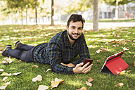 Portrait of smiling man with smartphone and tablet lying on meadow in autumn - JASF01290