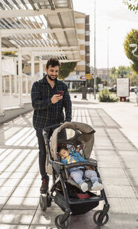 Father looking at his cell phone while his son sleeping in buggy - JASF01293