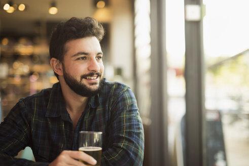 Smiling man sitting in a coffee shop looking through window - JASF01296