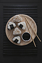 Onigiris, bowl with soy sauce and chopsticks on wooden plate - RTBF00530