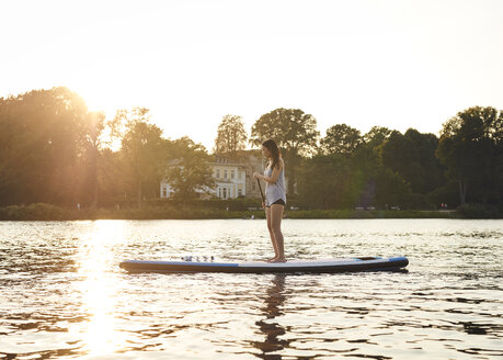 Germany, Hamburg, Young woman on paddleboard enjoying summer - WHF00037