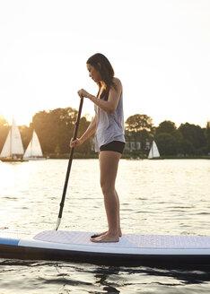Germany, Hamburg, Young woman on paddleboard enjoying summer - WHF00040