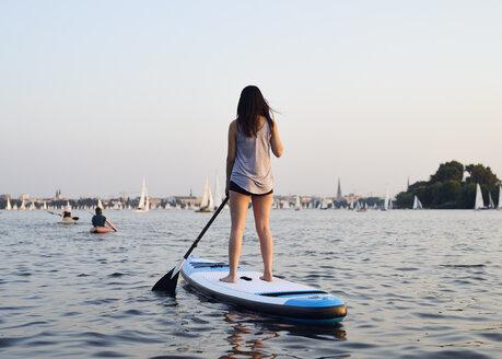 Germany, Hamburg, Young woman on paddleboard enjoying summer - WHF00043