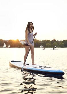 Germany, Hamburg, Young woman on paddleboard enjoying summer - WHF00046