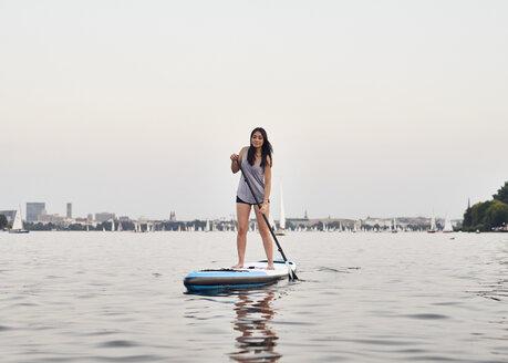 Germany, Hamburg, Young woman on paddleboard enjoying summer - WHF00049