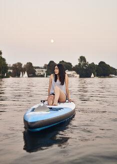 Germany, Hamburg, Young woman on paddleboard enjoying summer - WHF00052