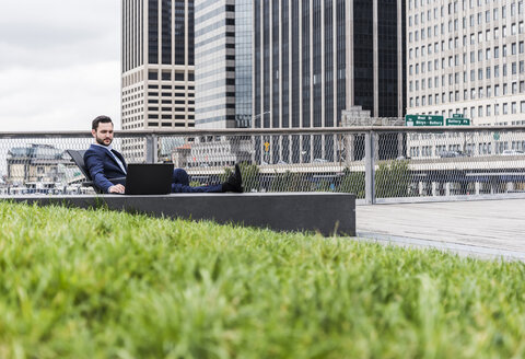 USA, New York, Manager in Manhattan sitting outdoor, using laptop - UUF09200