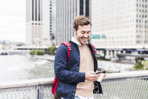 USA, New York, Businessan in Manhattan using smart phone and earphones - UUF09212