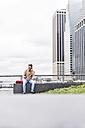 USA, New York, Businessan in Manhattan using smart phone and headphones - UUF09218