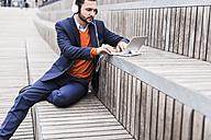 USA, New York City, Businessman sitting on stairs using digital tablet - UUF09227