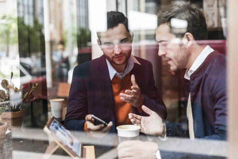 USA, New York City, Businessmen meeting in coffee shop, using mobile devices - UUF09233