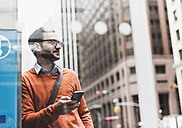 USA, New York City, Businessman leaning on ATM holding smart phone - UUF09239