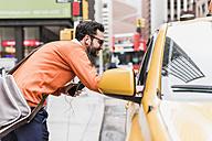 USA, New York City, Businessman talking to cab driver - UUF09245