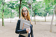 Smiling young woman holding a laptop and a notebook outdoors - GEMF01253