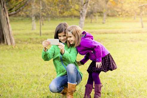 Two smiling sisters taking selfie with cell phone on a meadow in autumn - LVF05599