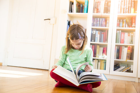 Little girl sitting on the floor watching turning pages of a book - LVF05603