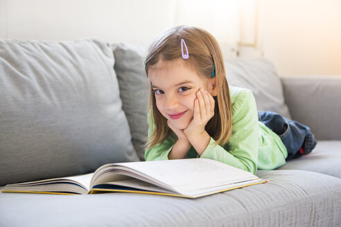 Portrait of smiling little girl lying on couch with a book - LVF05606