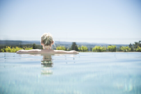 Woman standing in infinity pool, looking at distance - CHPF00328