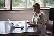 Businesswoman using cell phone in office - RIBF00595