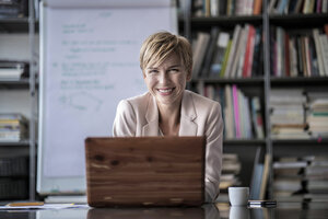 Portrait of smiling businesswoman with laptop in modern conference room - RIBF00598