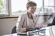 Businesswoman using futuristic modern computer in office - RIBF00604