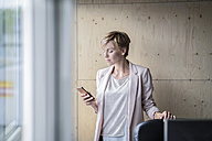 Businesswoman using cell phone in office - RIBF00607