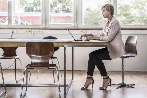 Businesswoman using laptop in modern conference room - RIBF00616