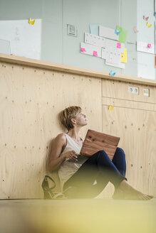 Businesswoman using laptop on the floor - RIBF00622