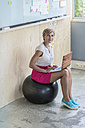 Smiling businesswoman sitting on fitness ball using laptop - RIBF00628
