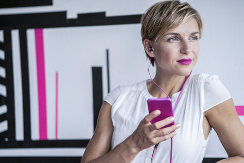 Woman in modern office listening to music on smartphone - RIBF00640