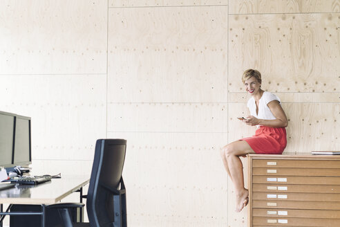 Smiling businesswoman sitting on filing cabinet in creative office - RIBF00646
